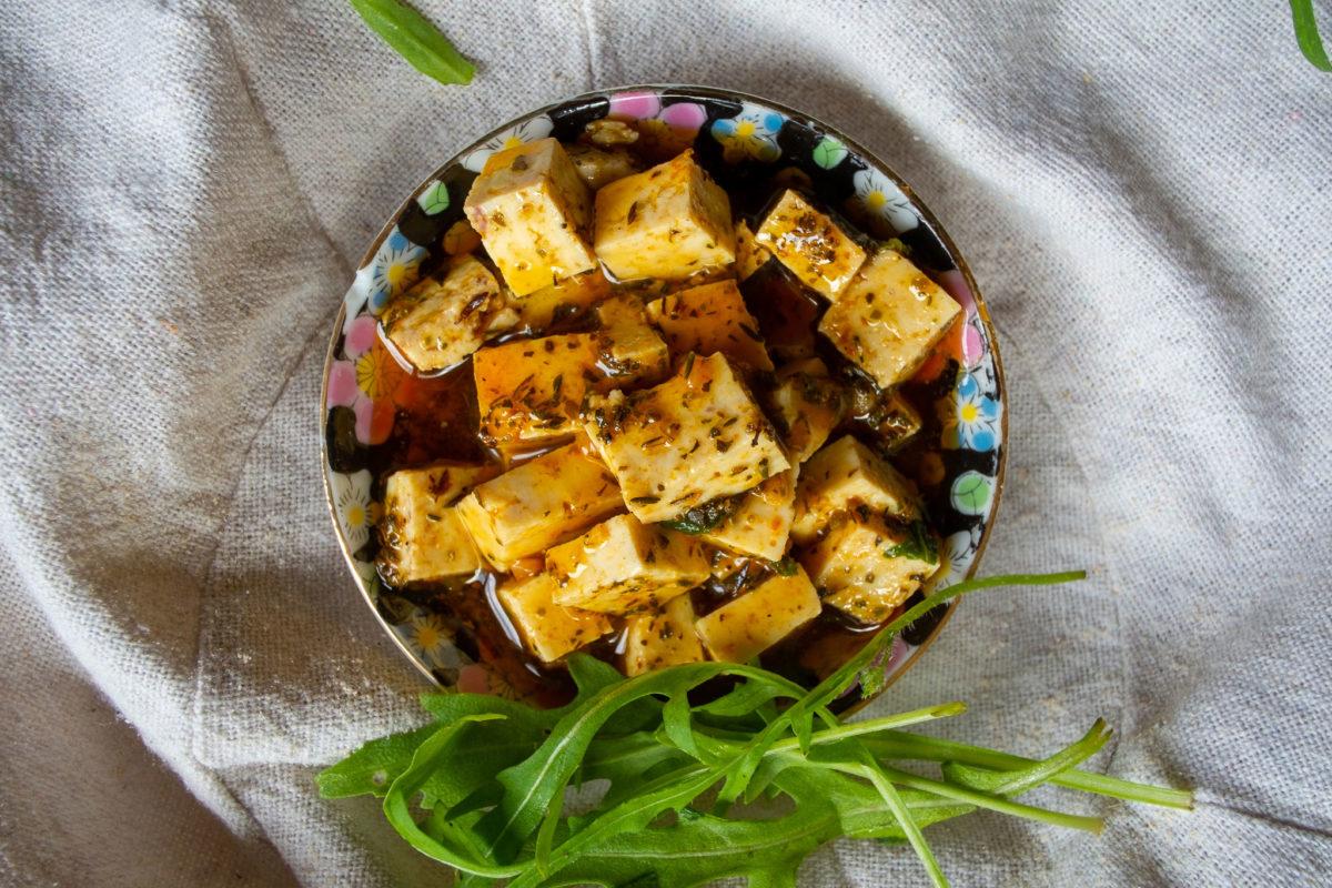 Teller mit marinierten Tofuwürfeln und Rauke